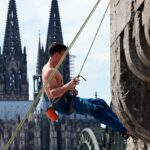 Climber on the Hohenzollernbrücke with a view on the cathedral